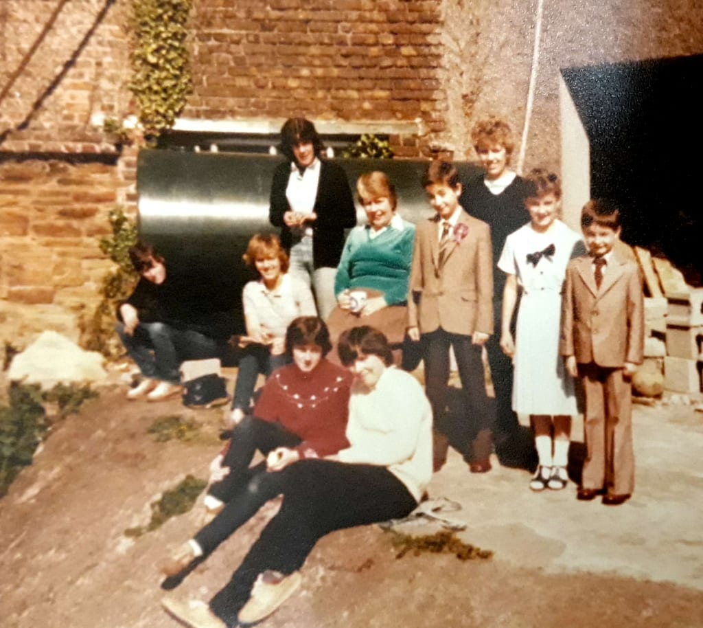 Suzanne and her brothers, Aiden and Declan, with the despatch workers - taken in the back yard of the Mills c. 1983.